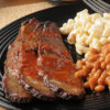 Brisket served with BBQ sauce, mac and cheese and beans