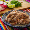 plate of cooked pork carnitas with vegetables